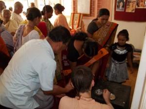 <h3> Sripad Tyagi Maharaja distributing charanamrita to the visitors</h3>